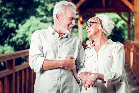 Buiten wandelen. Gezichtsportret van een aantrekkelijk, aantrekkelijk, vrolijk, vrolijk ouder wordend paar dat elkaar liefdevol aankijkt tijdens een wandeling in de buitenlucht