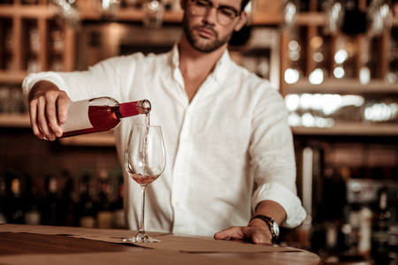 Small business. Concentrated bartender looking forward while pouring down wine into glass 스톡 콘텐츠