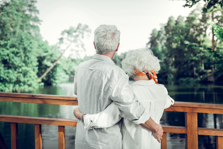 Couple back photo. Back photo of beautiful elderly white-haired loving caring couple wearing white clothing tenderly hugging each other.