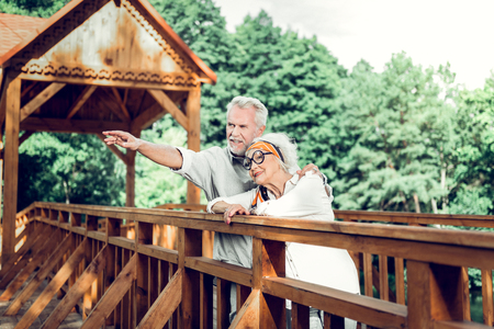 A couple on the bridge. Cheerful vigorous nice-looking vigorous joyful loving caring aged white-haired married couple standing on the wooden beautiful brown bridge