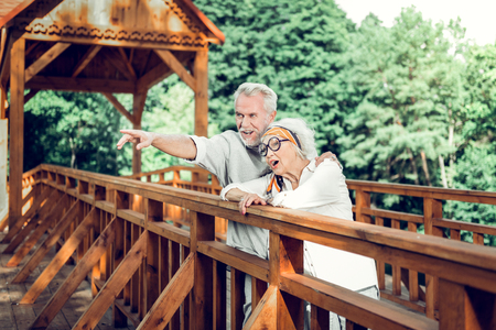 Walking spouses. Attractive good-looking happy contended loving caring aging silver-haired married wife and husband standing on the wooden bridge Stock Photo - 124983228