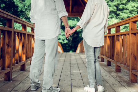 Close-up of hand in hand. Close-up photo of good-looking active vigorous elderly loving spouses in matching outfits holding hands while standing on the bridge. Stock Photo