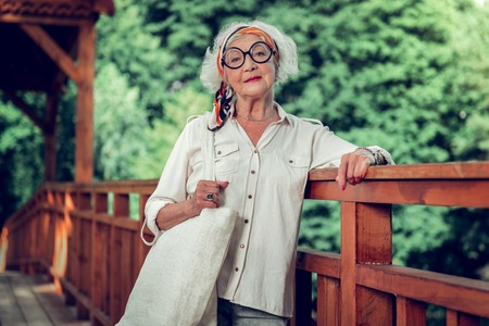Stylish elderly woman. Attractive joyful beaming fashionable white-haired stylish old lady wearing basic white shirt round-shaped eyeglasses and a bright headband posing on the wooden bridge outdoors 免版税图像
