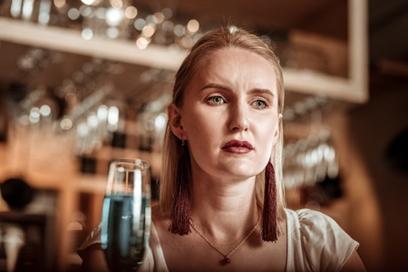 Facial expressions. Attractive woman being deep in thoughts while sitting in bar