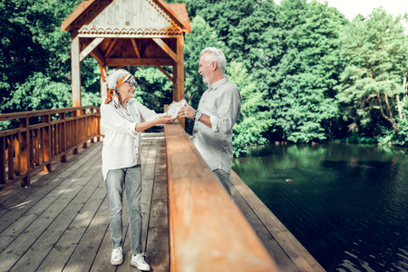 Spouses with a heart sign. Beaming glowing smiling contended joyful stylish elderlyd husband and wife wearing matching looks holding a heart sign in hands while standing on the wooden bridge