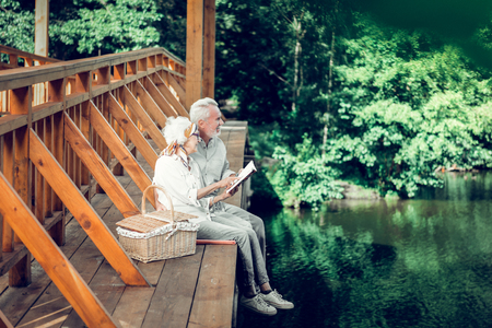 Reading outdoors. Merry smiling stylish glowing happy cheerful delightful silver-haired spouses in years sitting outdoors and enjoying a book Stock fotó