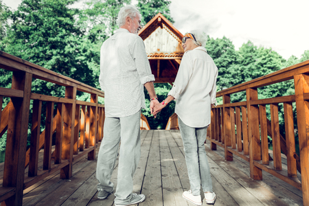 Holding hands. Happy appealing nice-looking cheerful elderly silver-haired loving married couple wearing matching outfits holding hands and standing on the bridge. Stock Photo