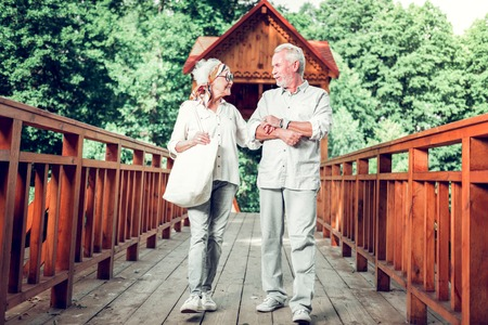 Walking down the bridge. Elderly beautiful nice-looking happy loving caring elderly white-haired couple in stylish clothing walking down the wooden bridge outdoors.