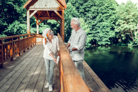Time together. Happy smiling contended charming stylish old white-haired spouses hanging a heart sign on the wooden bridge Stock Photo