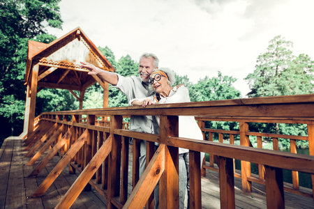 Enjoying the nature. Happy contended nice-looking appealing alluring old stylish silver-haired married couple standing on the wooden bridge and enjoying the nature scenery