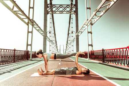 Summertime fitness. Two active young people stretching while doing yoga asanas outside at sunrise