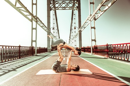 Pair yoga. Young slim girl being engaged in acrobatic yoga with her male partner Фото со стока