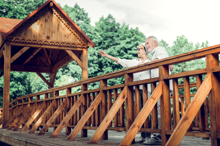 Elderly couple outside. Happy attractive nice-looking active vigorous cheerful joyful loving caring elderly silver-haired spouses standing on the wooden brown bridge and pointing at out.