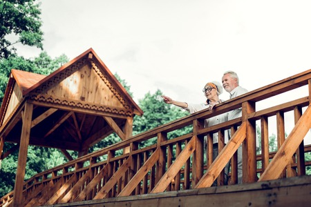 Woman and husband. Cheerful attractive good-looking joyful vigorous delightful aging stylish spouse and stylish eyeglasses standing on the bridge with handsome white-haired nice-looking man together
