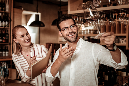 Just look. Delighted male person keeping smile on his face while demonstrating wineglass