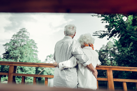 Embracing elderly spouses. Back photo of attractive alluring good-looking aging grey-haired spouses in stylish white clothing lovingly embracing each other