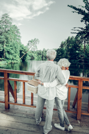 Enjoying the beautiful scenery. Full-sized picture of nice-looking attractive loving caring appealing elderly couple hugging and enjoying the beautiful scenery