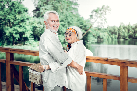 A couple with picnic basket. Delightful smiling alluring fashionable joyous aged female wearing eyeglasses cuddling a silver-haired handsome husband keeping a picnic wicker basket in hands