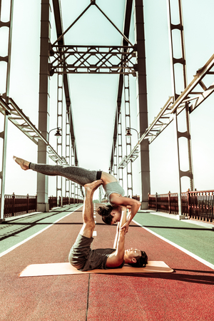 Training together. Two people doing an acrobatic exercise on a pedestrian bridge