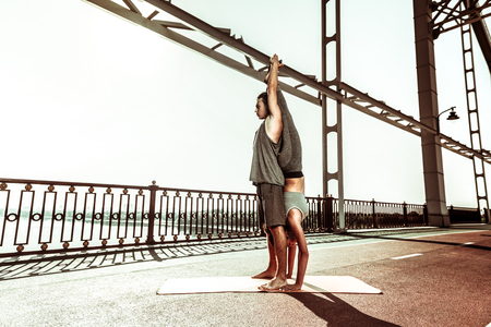 Upside down. Sporty girl holding a handstand on a mat on the bridge in pair with a fit young man Фото со стока