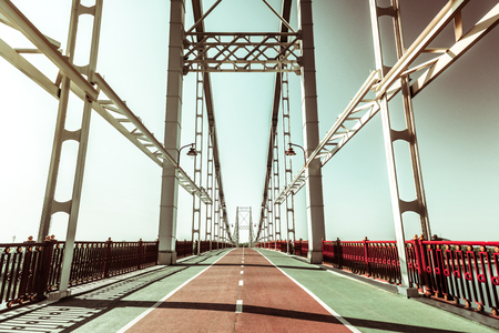 Suspension bridge. Panoramic view of an empty footbridge on a sunny day with blue sky in summer