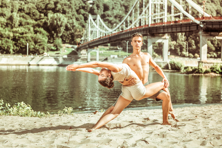 Acroyoga practice. Group of beautiful fit millennials standing in front of the bridge and doing stretching exercises together