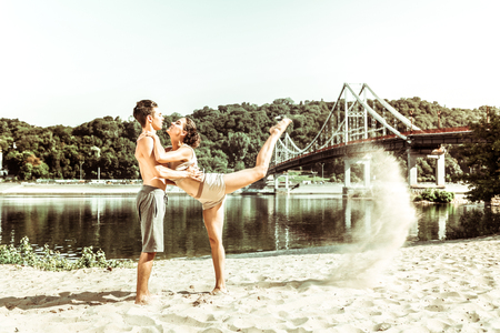 Flexibility and health. Pretty female yogi wearing a beige top and shorts leaning on a dark-haired partner while stretching outside