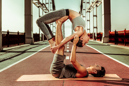 Flying wheel asana. Two attractive healthy people performing a flying wheel pose on an exercise mat Stockfoto