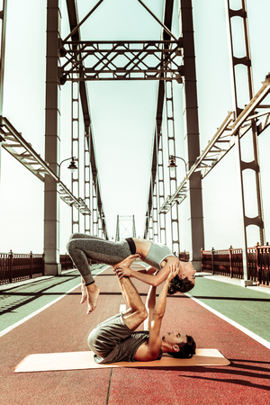 Partner yoga. Strong acroyogi supporting his female partner using his legs and arms while doing acroyoga outdoors