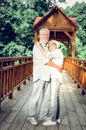 Elderly spouses in love. Happy contended alluring beautiful loving couple wearing stylish white clothing tenderly embracing each other while walking in the forest Stock Photo