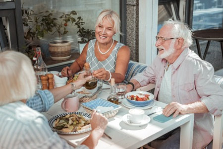 Thank you. Happy mature man going to eat salad while listening to funny stories Stock Photo