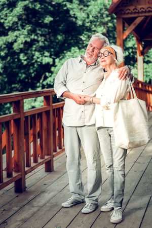 Cuddling aging spouses. Attractive cheerful joyful caring silver-haired aging male tenderly cuddling the elegant fashionable aged beautiful spouse while walking across the wooden bridge.