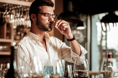 Stop the moment. Handsome man standing at the table while smelling cork from wine