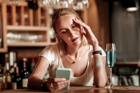 Deep in thoughts. Attentive female person sitting in bar and waiting for her boyfriend Фото со стока