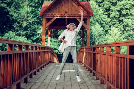 Jumping up on the bridge. Happy charming contended nice-looking laughing vigorous fashionable aged silver-haired lady in eyeglasses and casual clothing jumping up on the bridge outdoors 写真素材