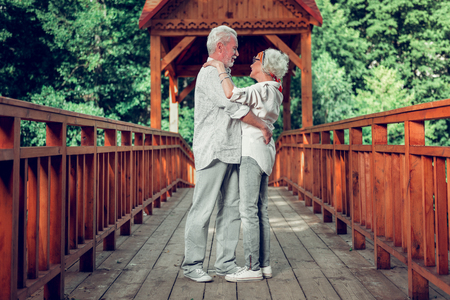 Embracing aging couple. Full-sized of beautiful loving caring appealing elderly white-haired spouses standing on the bridge and embracing each other