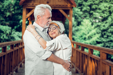 Hugging couple in years. Close-up portrait of elderly fashionable white-haired woman in eyeglasses tenderly hugging the handsome attractive aging bearded cheerful spouse outdoors