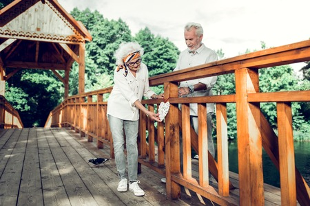 Spending time with a customer. Delightful charming fashionable stylish aging female with silver hair and head band hanging a heart sign on the bridge along with elderly white-haired attractive spouse Stock Photo - 124983375