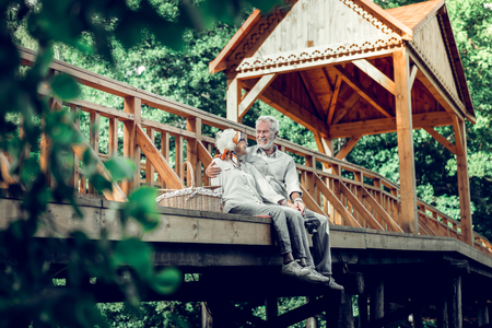 Man and woman on the bridge. Loving caring happy smiling cheerful beaming white-haired elderly man and woman tenderly looking at each other while sitting at the bridge.