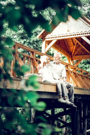 Being on the bridge. Loving caring joyful stylish smiling beaming silver-haired aging man and woman wearing modish clothing having conversation while sitting at the wooden bridge