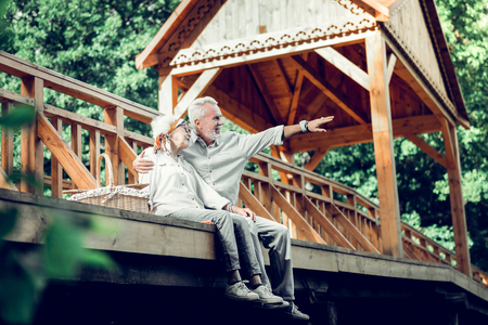 Beautiful elderly couple. Handsome loving white-haired good-looking caring aging husband tenderly cuddling his elderly appealing charming fashionable glowing wife while having a seat on the bridge.