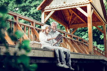 Reading a book. Carefree stylish glowing beautiful beaming silver-haired married couple in advanced years wearing stylish clothing reading a book on the wooden bridge