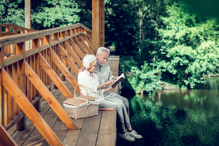 Time outdoors. Grinning glowing satisfied vigorous delightful white-haired spouses well in years sitting on the bridge outdoors and reading a book together