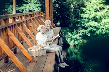 Reading together. Grinning contended stylish good-looking satisfied delightful spouses with white short hairdo in years spending time on the bridge while reading a book together