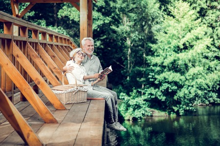 Time on the bridge. Appealing smiling happy contended fashionable nice-looking charming elderly spouses with grey short hairdo having a good time while reading a book together