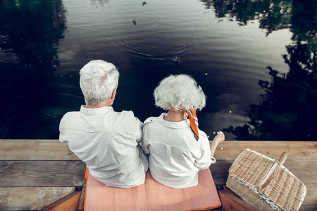 Back picture of a couple. Back shot of beautiful loving elderly attractive spouses in years with white short hairdo spending time on the lake