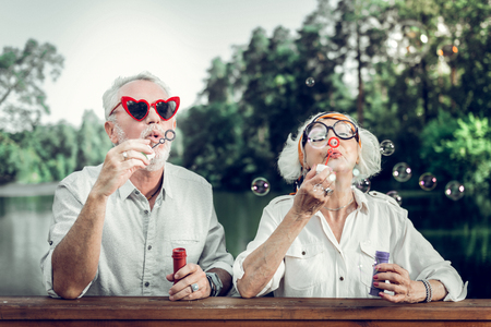 Blowing bubbles. Happy cheerful beaming glowing charming beautiful loving elderly couple in funny sunglasses blowing bubbles outdoors Stock Photo