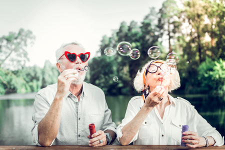 Elderly couple blowing bubbles. Face portrait of joyous cheerful beaming contended nice-appealing loving elderly man and wife wearing funny sunglasses engaging in blowing bubbles outdoors Stock Photo