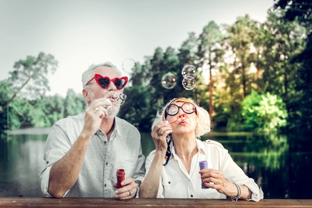 Bubbles blowing. Close-up portrait of joyful contended happy charming good-appealing beaming loving caring elderly husband and wife wearing stylish sunglasses having fun while blowing bubbles Stock Photo