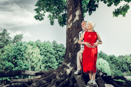 Beautiful elderly spouses. Attractive cheerful elderly white-haired man tenderly cuddling a charming delightful elegant aging wife in red dress while standing under the tree